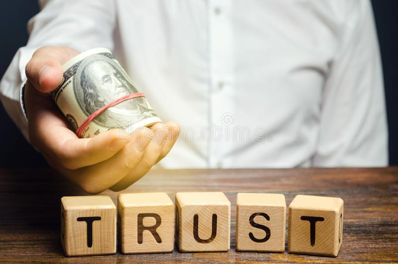 Wooden blocks with the word Trust and money in the hands of a businessman. Trust relationships between business partners, friends. Relatives. Respect and royalty free stock photo