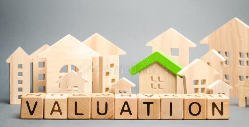Wooden blocks with the word Valuation and many houses. Resale residential property condition. The study of the state of the house stock images