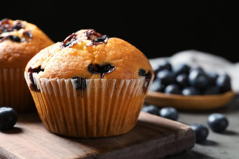 Wooden board with blueberry muffins on grey table against black background, closeup view royalty free stock photo