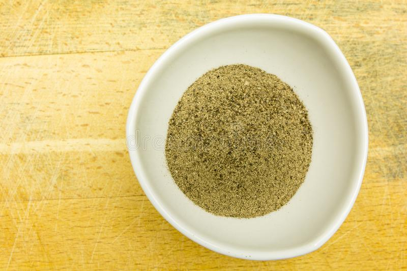 On a wooden board bowl with ground black pepper. View from above. stock photos