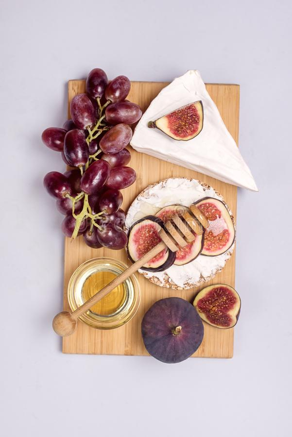 Wooden Board with Brie Cheese Figs Grapes and Honey Snack For Wine Autumn Harvest Food Vertical Top View.  royalty free stock photos