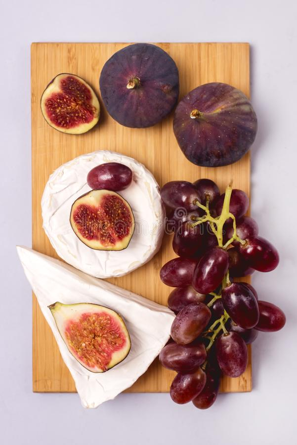 Wooden Board with Brie Cheese Figs and Grapes Snack For Wine Autumn Harvest Food Vertical Top View.  stock photography