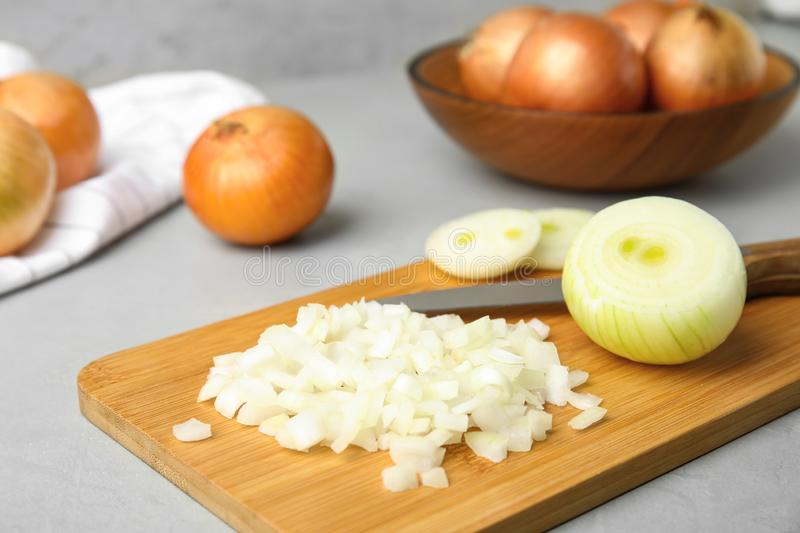 Wooden board with cut onion and knife. On grey table royalty free stock photos