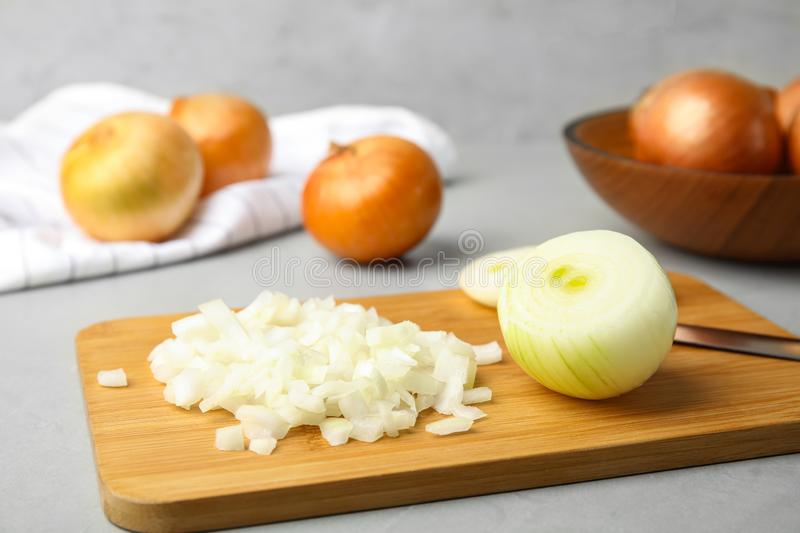 Wooden board with cut onion and knife. On grey table royalty free stock photo