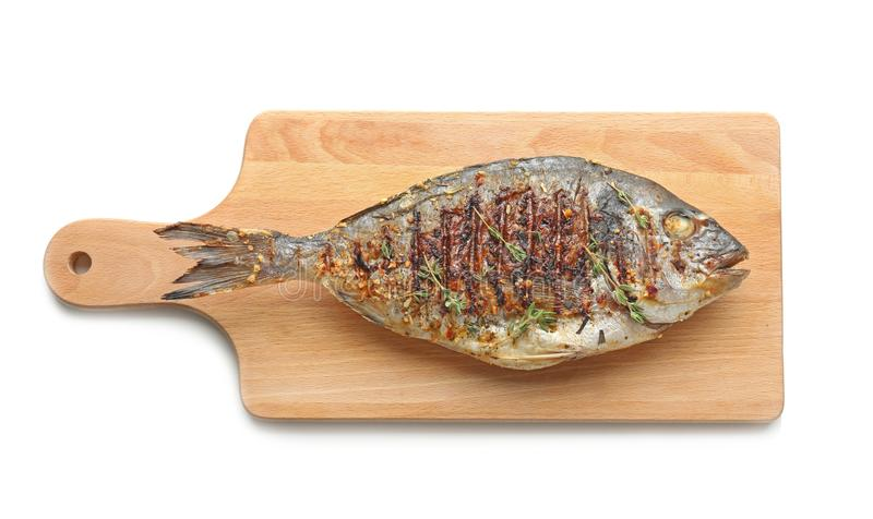 Wooden board with delicious fried fish royalty free stock image