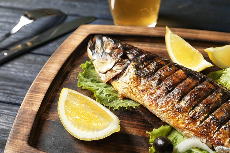 Wooden board with delicious grilled fish, closeup royalty free stock image