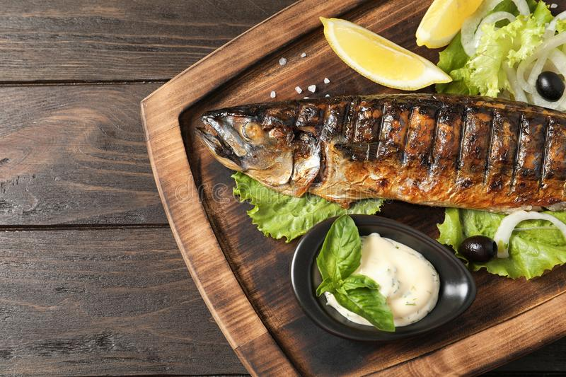 Wooden board with delicious grilled fish on table. Top view stock images