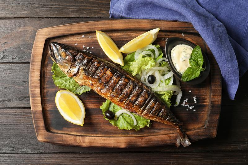 Wooden board with delicious grilled fish. On table, top view royalty free stock photo