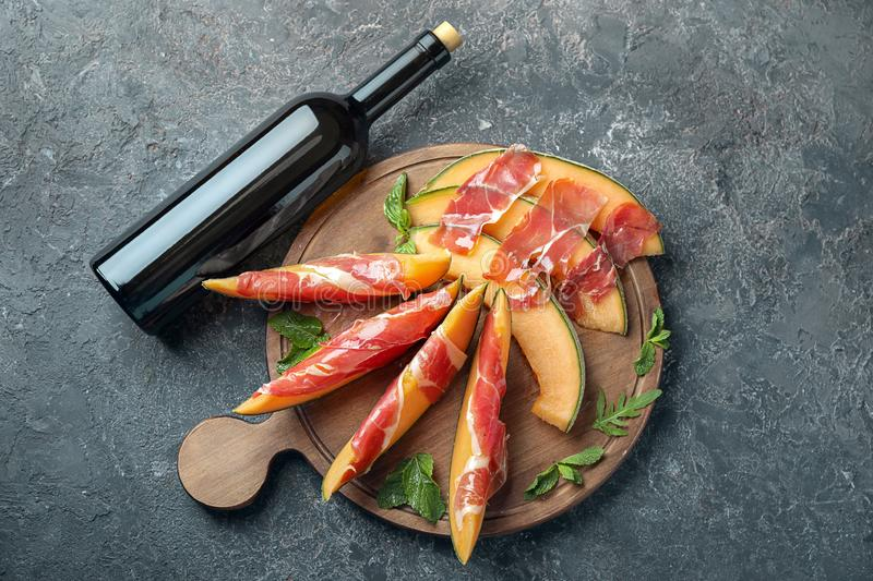 Wooden board with delicious melon and prosciutto near bottle of wine on table royalty free stock photography