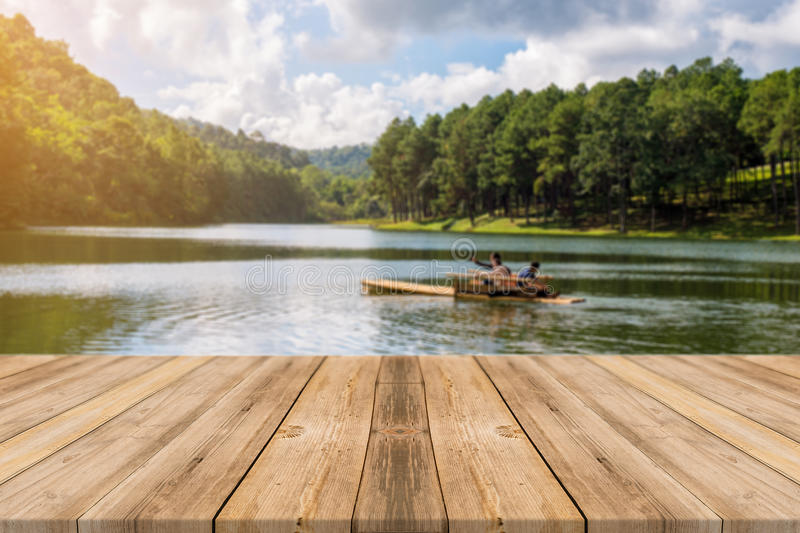 Wooden board empty table blur lake in forest background. royalty free stock image