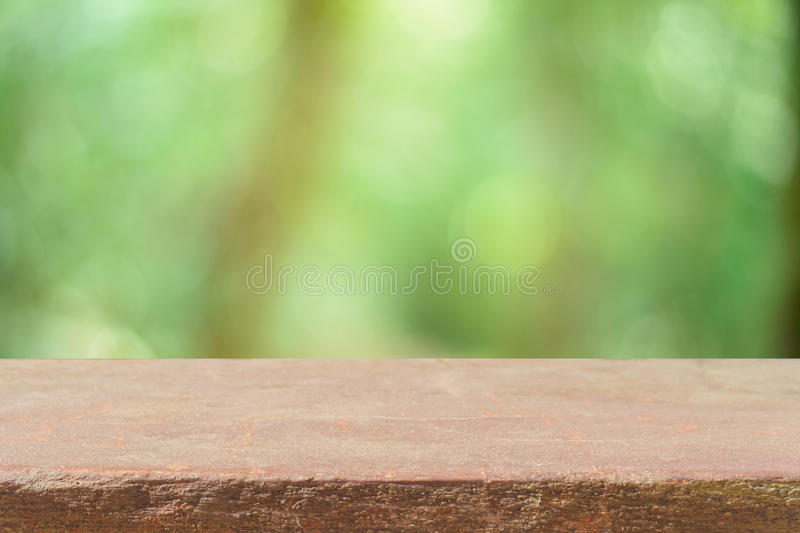 Wooden board empty table blur trees in forest background - can be used for display or montage your products. Wooden board empty table in front of blurred royalty free stock photography