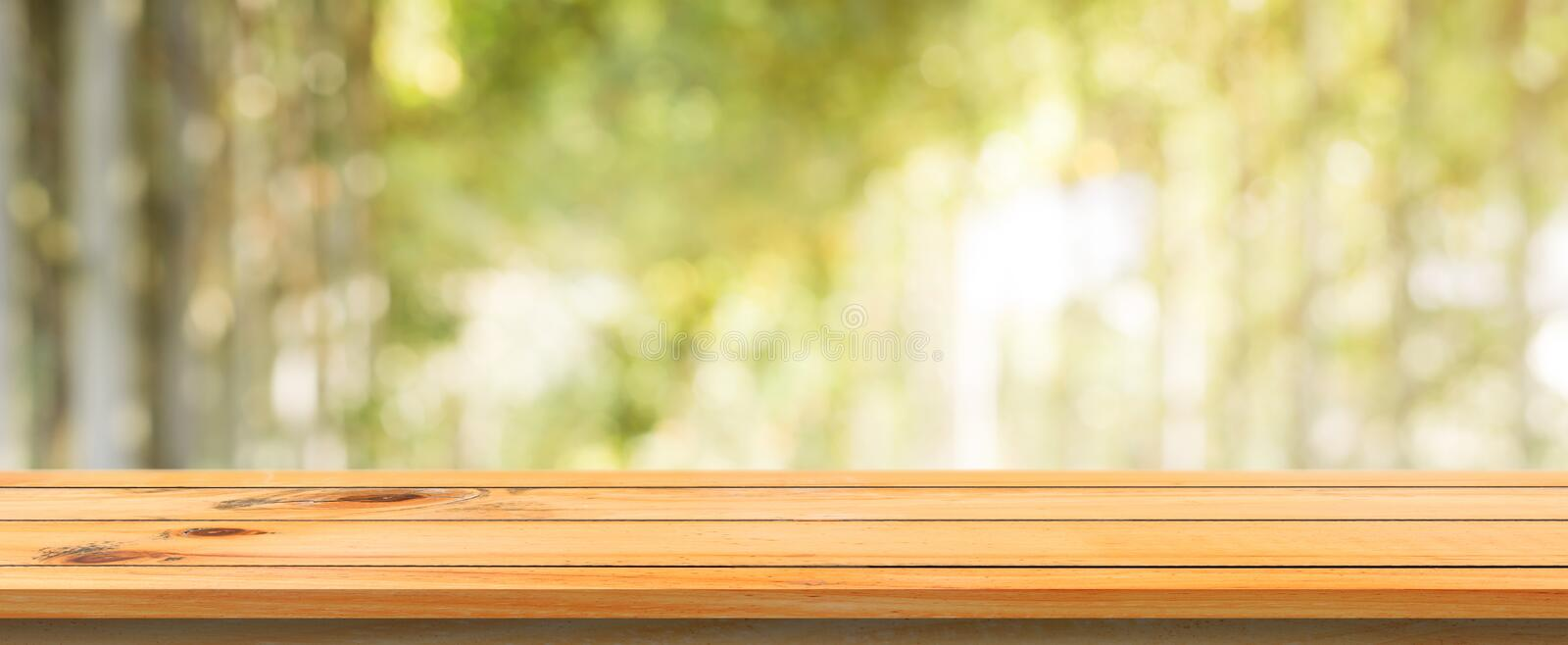 Wooden board empty table blurred background. Perspective brown wood table over blur trees forest background. royalty free stock photography