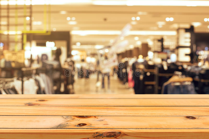 Wooden board empty table blurred background. Perspective brown wood table over blur in department store background. stock photo