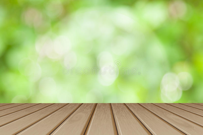 Wooden board empty table in front of blurred background. Perspective brown wood table over blurred trees with bokeh background - stock photos