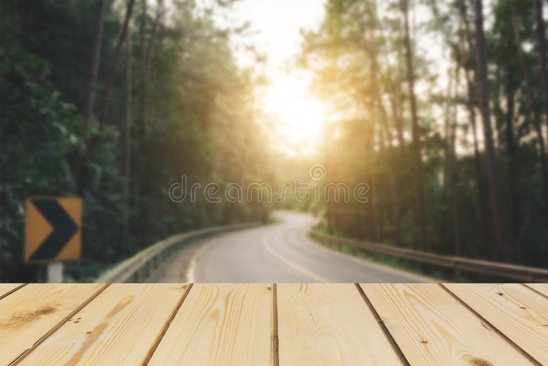 Wooden board empty table in front of blurred background. Perspective brown wood over road is surrounded by pine trees forest to th stock images
