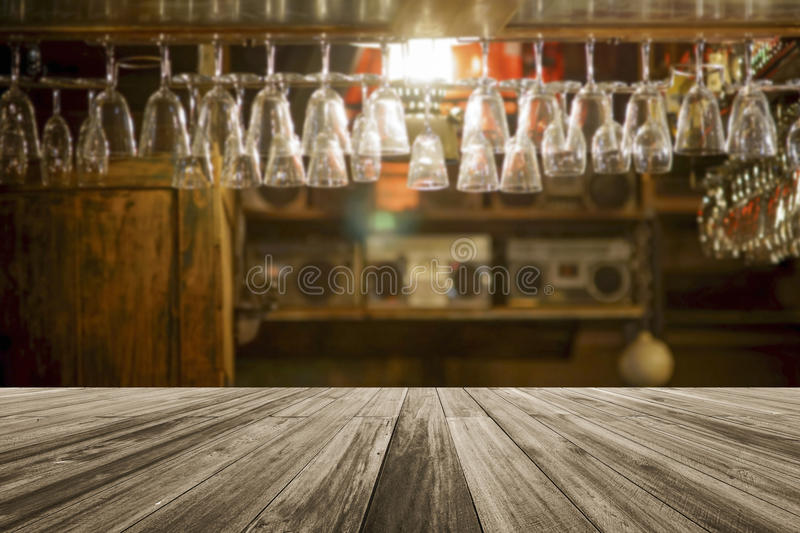Wooden board empty table in front of blurred glass hanging upside down on a shelf at bar background royalty free stock image
