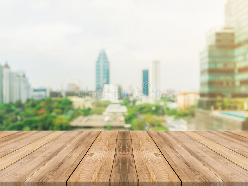 Wooden board empty table top blurred background. Perspective brown wood table over blur city building view background stock photo