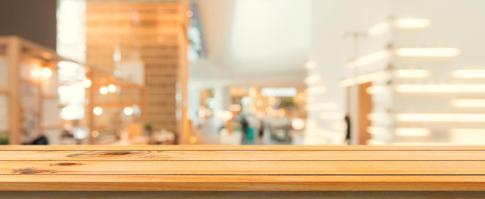 Wooden board empty table top blurred background. Perspective brown wood table over blur in coffee shop background.Panoramic banner. Wooden board empty table top royalty free stock image