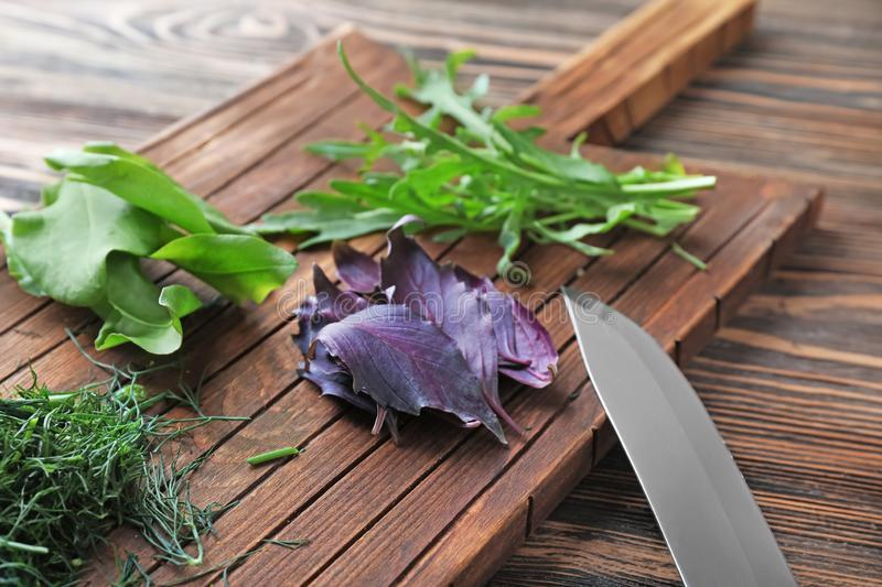 Wooden board with fresh herbs and knife on table, closeup royalty free stock photography