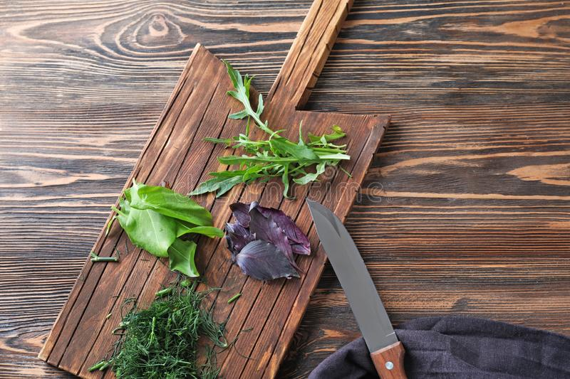 Wooden board with fresh herbs and knife on table stock photo