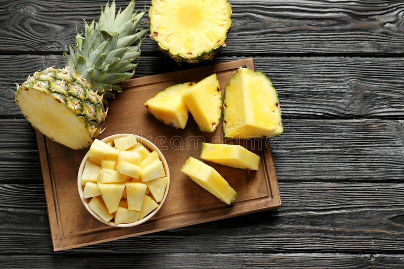Wooden board with fresh sliced pineapple. On table, top view stock photos