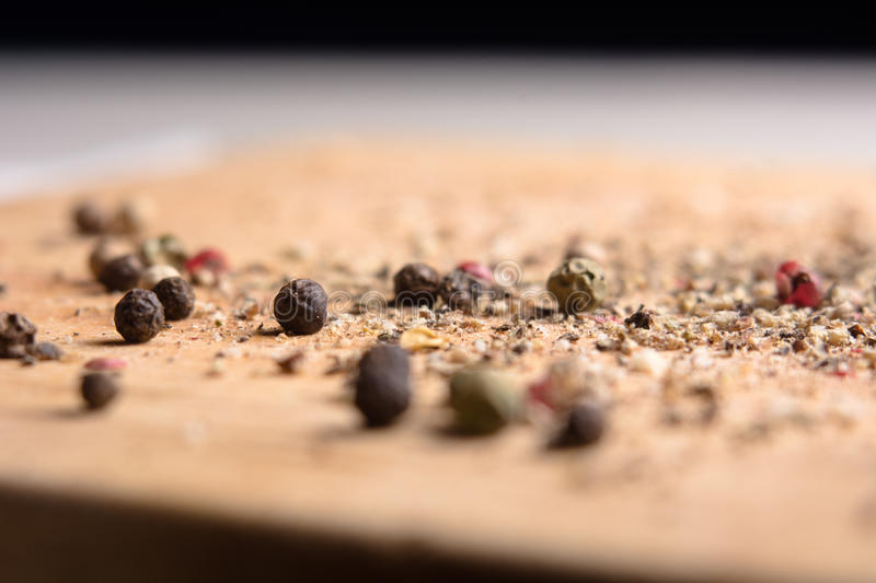 On a wooden board, ground pepper and peas. Close-up of a wooden background with black, green and red bell pepper royalty free stock photos