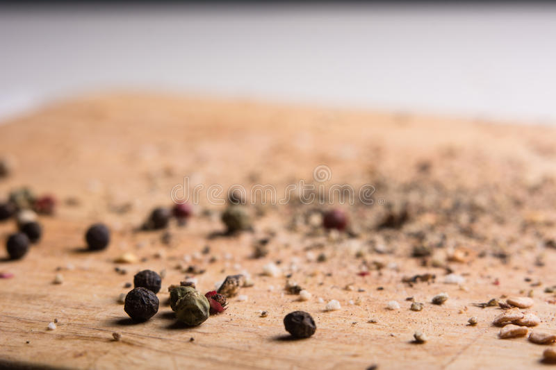 On a wooden board, ground pepper and peas. Close-up of a wooden background with black, green and red bell pepper stock photography