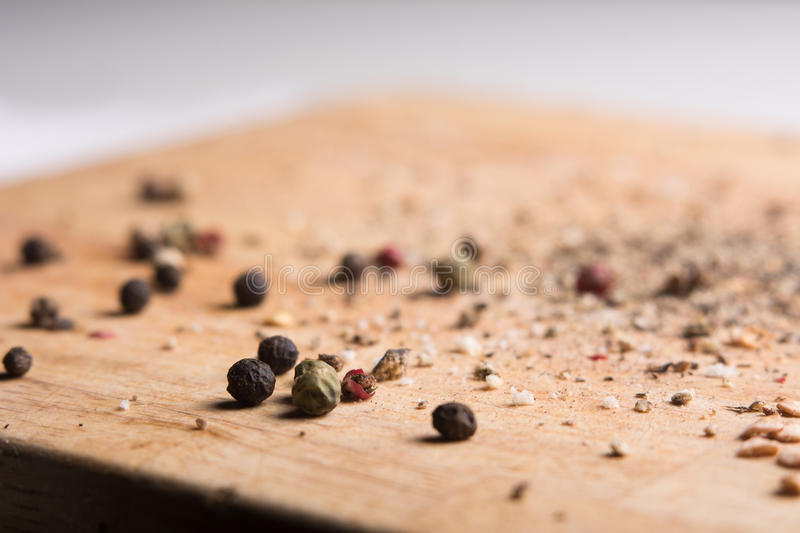 On a wooden board, ground pepper and peas. Close-up of a wooden background with black, green and red bell pepper royalty free stock photography