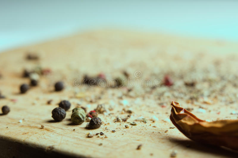 On a wooden board, ground pepper and peas. Close-up of a wooden background with black, green and red bell pepper and cayenne red pepper royalty free stock photos