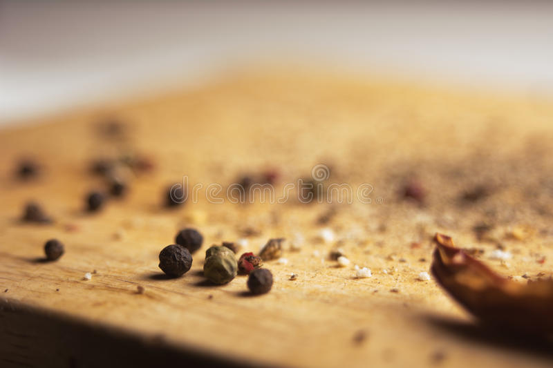 On a wooden board, ground pepper and peas. Close-up of a wooden background with black, green and red bell pepper and cayenne red pepper royalty free stock photography