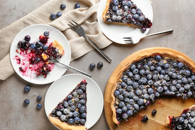 Wooden board and plates with delicious blueberry pie on table stock images