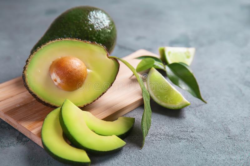 Wooden board with ripe avocados and lime on grey textured background royalty free stock photography