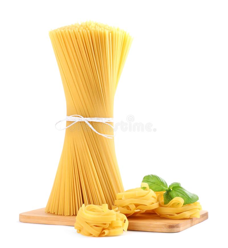 Wooden board with spaghetti, tagliatelle pasta and basil leaves isolated on white. Wooden board with spaghetti, tagliatelle pasta and basil leaves isolated stock photos