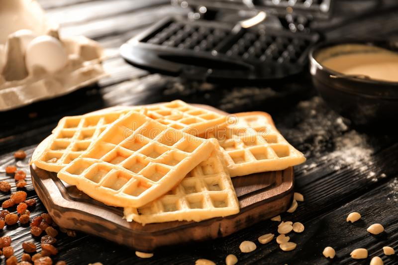 Wooden board with tasty Belgian waffles on dark wooden table stock photography