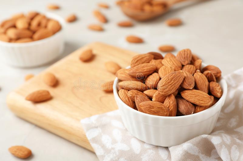 Wooden board with tasty organic almond nuts in bowl on table. royalty free stock photo