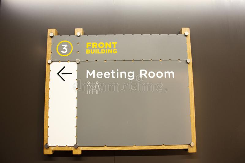 Wooden board or wood label for direct guide go to meeting room inside of office building stock image
