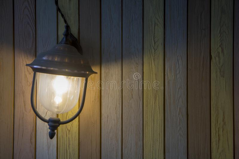 Wooden boards fence yellow, blue, red pastel colors. old luminous electric bulb. vertical lines. rough surface texture royalty free stock photo