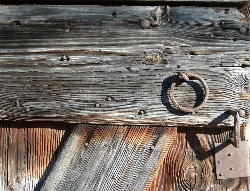 Part of a medieval barn door with wood grain and iron rings. Wooden boards of an old gate with visible wood grain, Iron fittings in a very old wooden gate stock image
