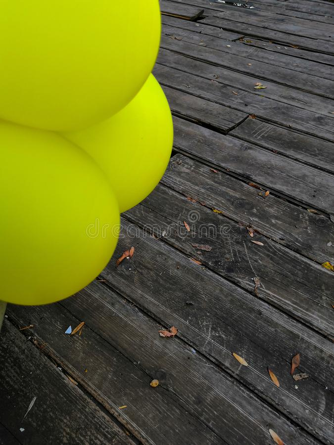 Wooden boards and yellow balloons background. Colorful balloons on wooden table. Blue, bright, decoration, design, holiday, summer, air, anniversary, beautiful royalty free stock image