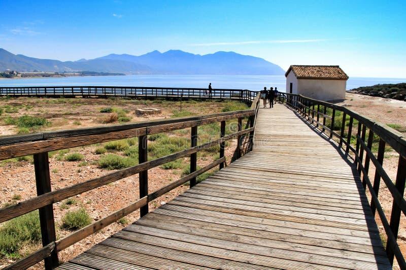Wooden boardwalk along the beach in Isla Plana village. Isla Plana, Murcia, Spain-October 8, 2019:Wooden boardwalk along the beach in a sunny day in Isla Plana stock images