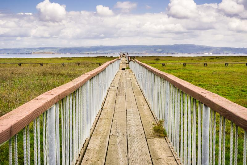 Wooden boardwalk. Damaged wooden boardwalk going over the marshes of south San Francisco bay area, Palo Alto Baylands Park, California stock image