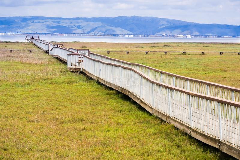 Wooden boardwalk. Damaged wooden boardwalk going over the marshes of south San Francisco bay area, Palo Alto Baylands Park, California stock photo