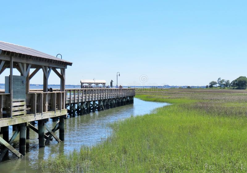 A wooden boardwalk going through marsh wetlands royalty free stock photography