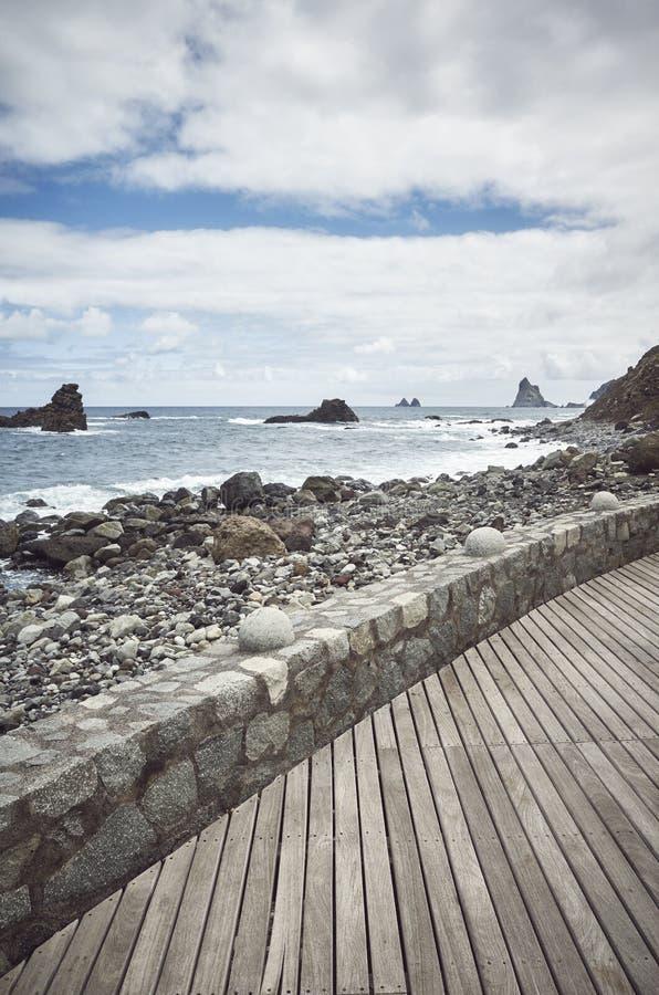 Wooden boardwalk by the Roque de Las Bodegas Beach, Tenerife, Spain. Wooden boardwalk by the Roque de Las Bodegas Beach, retro color toning applied, Tenerife stock image