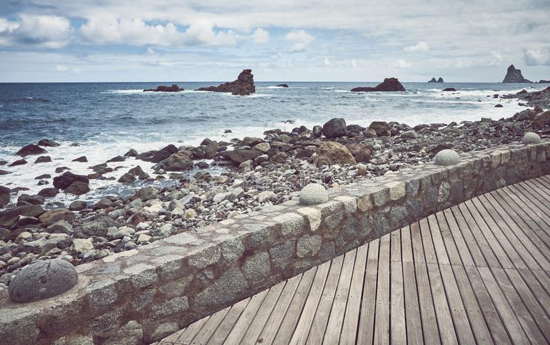 Wooden boardwalk by the Roque de Las Bodegas Beach, Tenerife, Spain. Wooden boardwalk by the Roque de Las Bodegas Beach, retro color toning applied, Tenerife royalty free stock image
