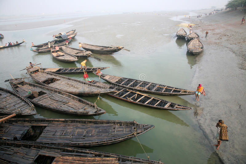 Wooden boat crosses the Ganges River in Canning Town, West Bengal, India. To use a small wooden is easy, fast and cheap way how to cross the Ganges River royalty free stock photos