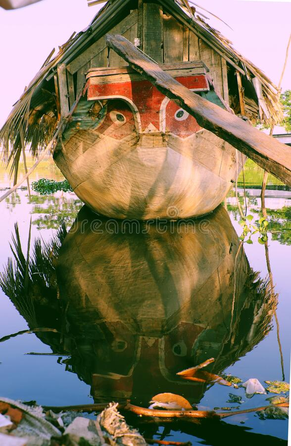 Wooden boat with dried leaves roof, eyes looking straight mooring at river reflect on water, Ho Chi Minh city, Vietnam royalty free stock photos