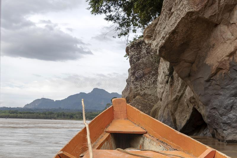 Wooden boat front and green jungle landscape, sailing in the muddy water of the Beni river, Amazonian rainforest, Bolivia. Contrast or orange wooden boat front royalty free stock image