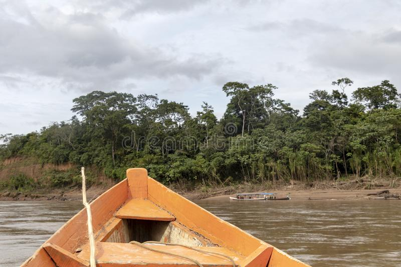 Wooden boat front and green jungle landscape, sailing in the muddy water of the Beni river, Amazonian rainforest, Bolivia. Contrast or orange wooden boat front royalty free stock images