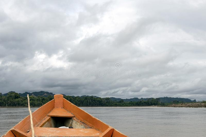 Wooden boat front and green jungle landscape, sailing in the muddy water of the Beni river, Amazonian rainforest, Bolivia. Contrast or orange wooden boat front royalty free stock photo